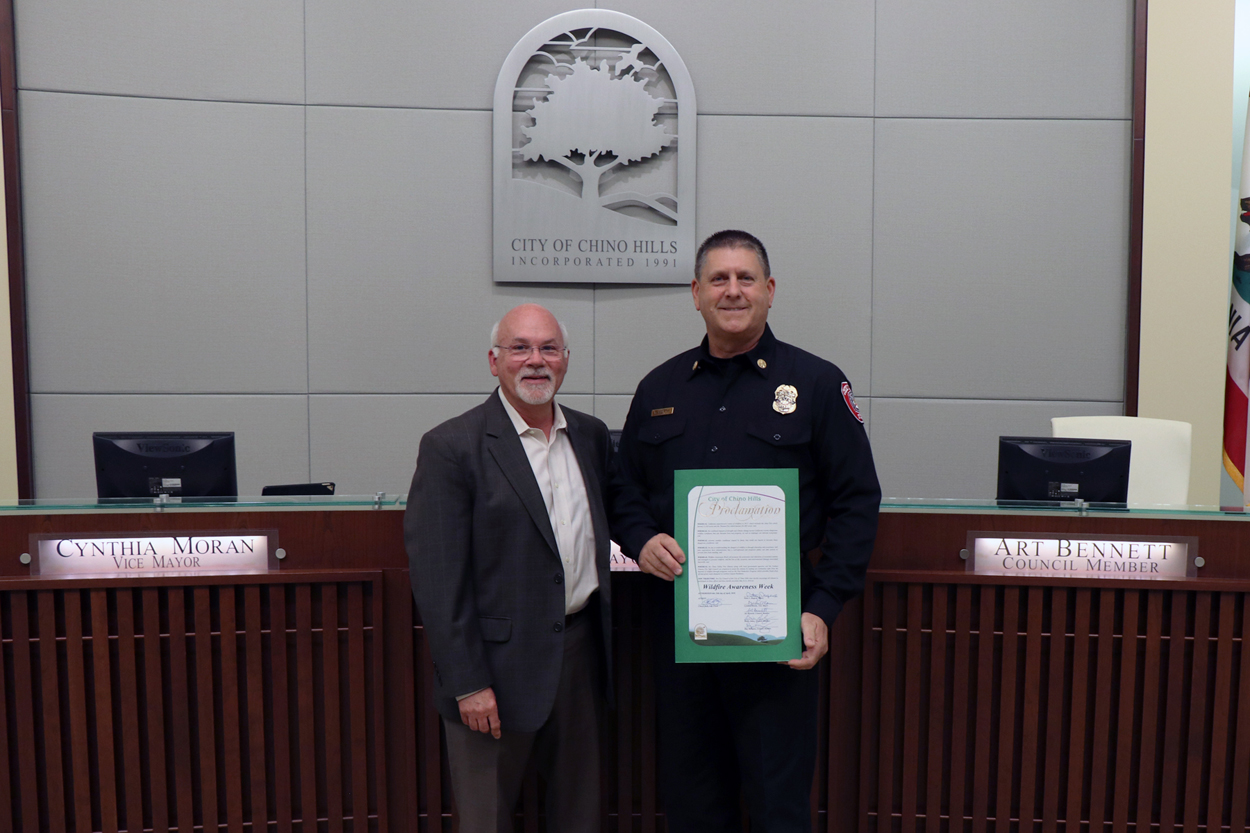 Deputy Chief Faherty accepting proclamation from Mayor Rogers
